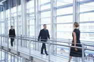 Stock Photo of Business People Walking By Railing In Modern Office