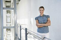 Stock Photo of Businesswoman Standing Arms Crossed In Office Corridor