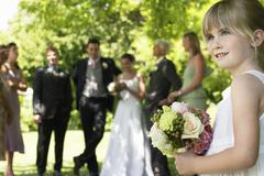 Cute Little Bridesmaid Holding Bouquet In Lawn Stock Photos