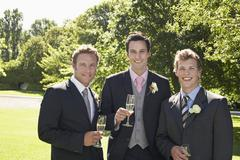 Men Holding Champagne Flutes At Wedding - stock photo