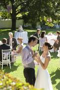 Newlywed Couple Toasting Champagne Among Wedding Guests Stock Photos