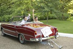 Stock Photo of Newlywed Couple Waving In Convertible