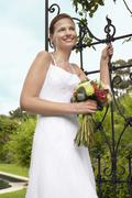 Stock Photo of Bride With Bouquet Standing By Gate