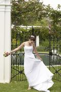 Stock Photo of Cheerful Bride Standing At The Entrance Of Garden