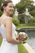 Stock Photo of Bride Holding Bouquet At Poolside
