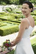 Bride Holding Bouquet In Formal Garden - stock photo