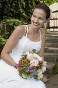 Stock Photo of Bride With Bouquet Of Roses Smiling