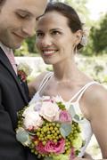 Bride And Groom Embracing In Garden - stock photo