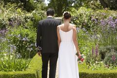 Newlywed Couple Walking In Garden - stock photo
