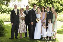 Newlywed Couple With Wedding Guests In Garden - stock photo