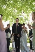 Bride And Groom Being Showered With Flower Petals - stock photo