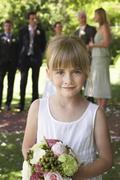 Cute Little Bridesmaid Holding Bouquet In Garden - stock photo