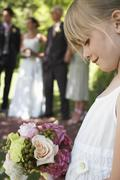 Cute Little Flower Girl Holding Bouquet In Garden - stock photo