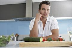 Young Man Looking Away In Domestic Kitchen - stock photo