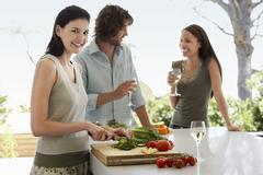 Woman Chopping Vegetables With Friends Communicating At Kitchen Counter Stock Photos