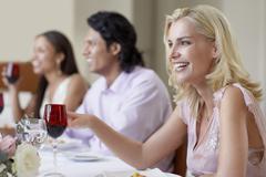 Cheerful Woman Enjoying Dinner Party With Friends - stock photo
