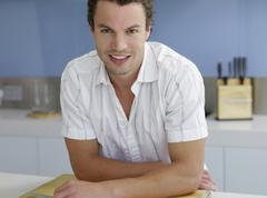 Confident Man Leaning At Kitchen Counter - stock photo