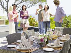 Fine Dining Table Setting With Friends In Background - stock photo