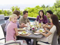 Stock Photo of Woman With Friends Enjoying Meal At Patio
