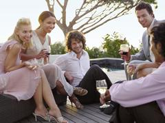 Friends Drinking And Socialising On Porch - stock photo