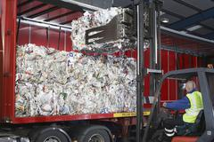 Worker Loading Stacks Of Recycled Papers On To Lorry - stock photo