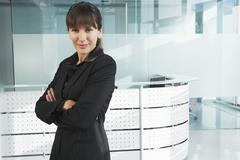 Stock Photo of Confident Businesswoman In Front Of Reception Desk