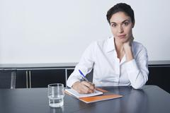 Businesswoman Writing Notes At Conference Table - stock photo