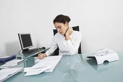 Businesswoman Writing On Document At Office Desk Stock Photos