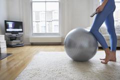 Woman Fitness Ball television katselu Kuvituskuvat
