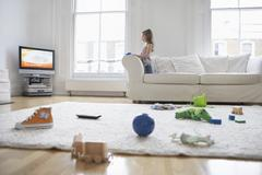 Girl Watching TV With Toys On Floor - stock photo