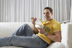 Man Eating Noodles From Takeaway Tray At Home - stock photo