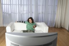 Onnellinen mies katsomassa televisiota sohvalla Kuvituskuvat
