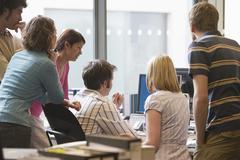 Multiethnic Executives Around Colleague Using Computer - stock photo