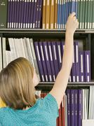 Young Woman Reaching For Book From Library Shelf - stock photo