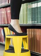 Lowsection Of Woman On Stool Reaching For Book - stock photo