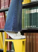 Lowsection Of Man On Stool Reaching For Book Stock Photos