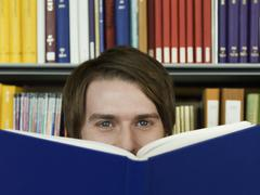 Stock Photo of Young Man Peeking Over Opened Book