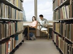 College Students Doing Homework In Library - stock photo