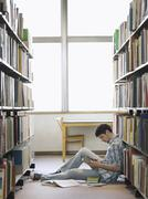 College Student Reading In Library - stock photo