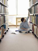 Student Reaching For Book In Library - stock photo