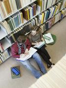 Students Doing Homework On Floor In Library Stock Photos