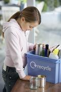 Girl Putting Empty Vessels Into Recycling Container - stock photo
