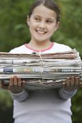 Smiling Girl Holding Bundle Of Waste Paper - stock photo