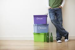 Stock Photo of Man Leaning Against Wall By Recycling Containers