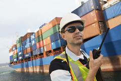 Man Using Walkie Talkie At Container Terminal - stock photo