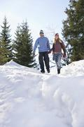 Couple Walking Down Snow Covered Hill Stock Photos