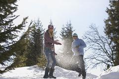 Stock Photo of Couple Playing In Snow On Hill