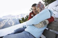 Man Embracing Woman On Bench Snowy Hillside - stock photo