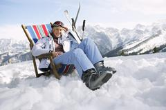 Female Skier Sitting On Deckchair In Mountains Stock Photos