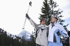 Cheerful Skiing Couple In Warm Clothing With Skis - stock photo